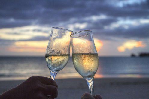 Обои Два запотевших бокала с охлажденным белым вином на песке морского пляжа, на закате солнца