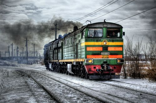 Обои Локомотив темно-зеленого цвета едет по заснеженным рельсам в хмурый день