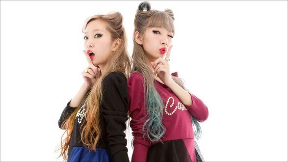 Обои Две азиатки приложили палец к губам, стоя спиной друг к другу на белом фоне