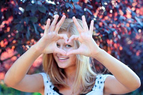 Обои Улыбающаяся девушка делает знак в виде сердца руками