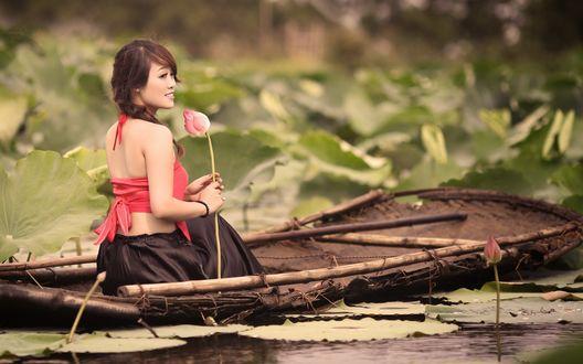 Обои Девушка сидит в лодке, держа в руках бутон лотоса, вокруг листья и бутоны лотосов