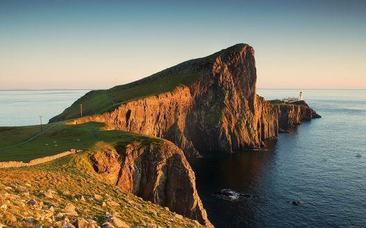 Обои Закат над морем с диким скалистым берегом, с белой башенкой маяка вдали