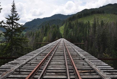 Обои Старый заброшенный мост с проложенными рельсами на фоне горного пейзажа