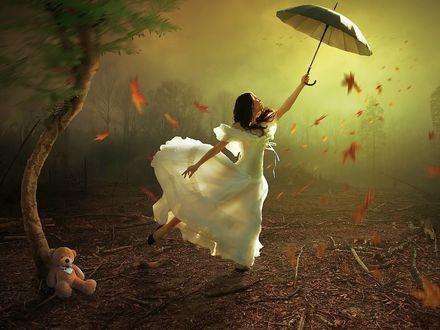 Обои Девушка в белом платье с раскрытым зонтом танцует под листопадом, на переднем плане одинокое дерево с сидящим у его подножия плюшевым мишкой, на фоне густой мглы