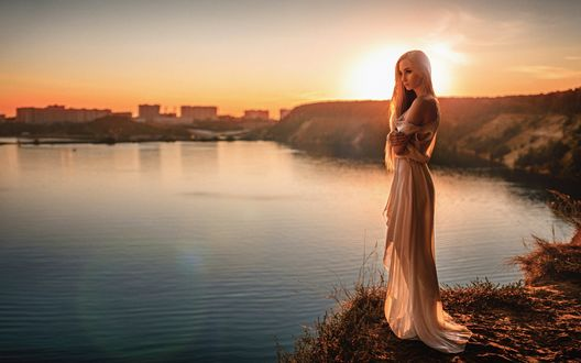 Обои Девушка в длинном платье стоит на холме у озера, на фоне заката