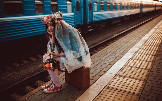 Обои Девушка с букетом цветов, в кроссовках и подвенечной фате, ожидая поезда, сидит на чемодане