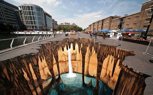 Обои Эффектная 3d граффити изображающая провал в живописную пещеру с мини водопадом и подземным озером на городской улице, by Edgar Mueller / Эдгар Мюллер