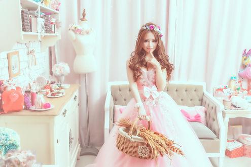 Обои Азиатка в венке и бальном розовом платье с корзинкой в руке, стоит по средине своей комнаты