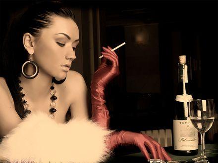 Обои Девушка в красных перчатках и украшениях задумчиво курит, сидя за столом перед бокалом вина и бутылкой
