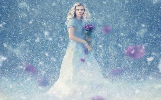 Обои Белокурая девочка в длинном, голубом платье с букетом сиреневых роз в руках стоит под снегопадом