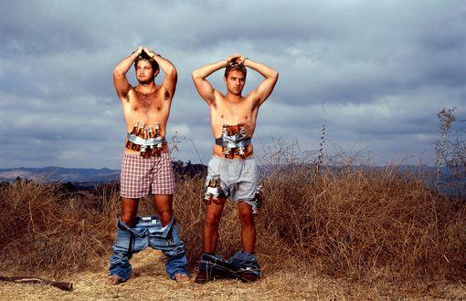 Обои Двое мужчин, держа руки в наручниках над головой, стоят в приспущенных джинсах и семейных трусах, на их талиях в качестве взрывного устройства закреплено пиво в различной таре, фото Ted Sabarese / Теда Сабарезе