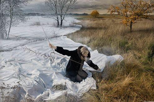 Обои Девушка сидит на белом полотне и сшивает его большой иглой, укрывает им землю и траву, превращая золотую осень в снежную зиму, by Eric Johansson / Эрик Йоханссон