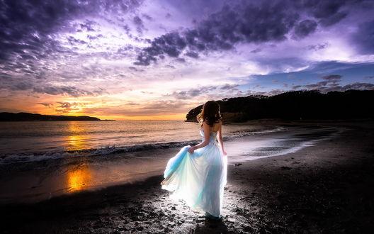 Обои Девушка в белом платье стоит на берегу моря и смотрит на закат солнца
