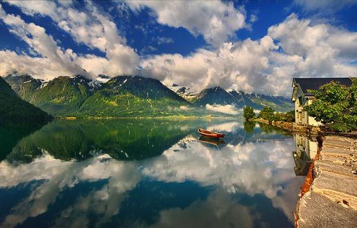Обои Лодка на воде перед домом, под облачным небом с отражением в воде, by Krzysztof Browko