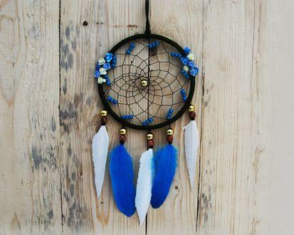 Обои Ловец снов с синими и белыми перьями на деревянной стене