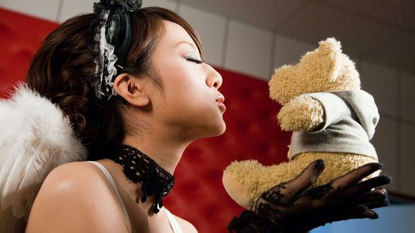 Обои Девушка азиатской внешности в черных перчатках, с белыми крыльями из перьев за спиной, держит маленького плюшевого медвежонка, закрыла глаза и готова его поцеловать