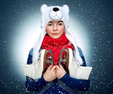 Обои Девушка в шапке в виде белого медведя, в красном теплом шарфике, с коньками в руках, стоит под падающими снежинками