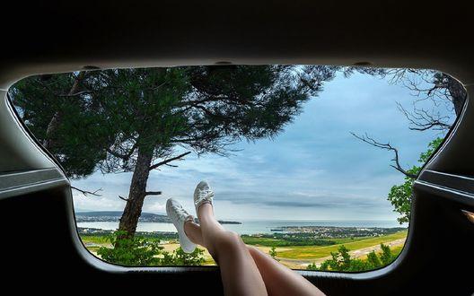 Обои Девушка выставила ножки в окно авто, из которого открывается пейзаж