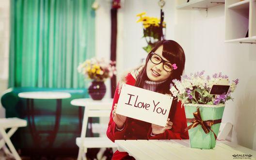 Обои Азиатская девушка сидит за столиком, на котором стоит букет цветов, с табличкой в руках, на которой надпись: I love you / Я тебя люблю, фотограф Salen
