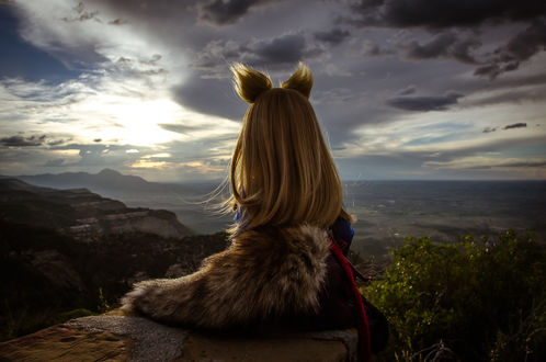 Обои Кукла Horo / Хоро из аниме Spice and Wolf / Волчица сидит на краю горы с видом на пейзаж