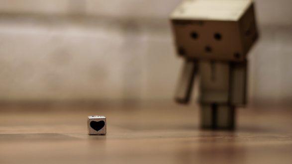 Обои Данбо стоя на полу смотрит грустным взглядом на лежачий кубик с сердечком