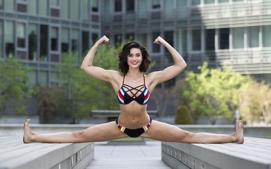 Обои Спортивная фигура и растяжка актрисы Bianca Van Damme / Бьянки Ван Варенберг, которая села на шпагат на фоне здания
