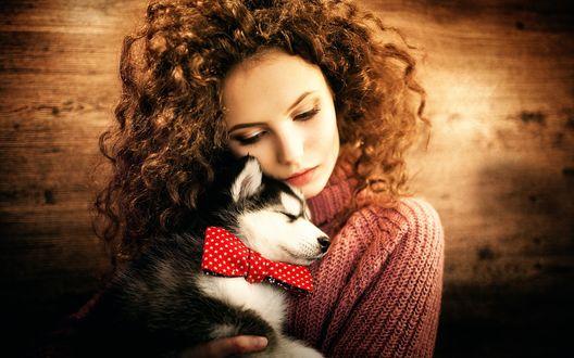 Обои Девушка с кучерявыми волосами держит на руках щенка хаски
