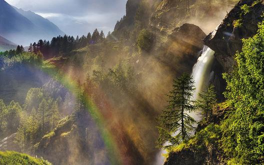Обои Крутой склон горы с деревьями и водопадом, освещенный яркими лучами солнца с радугой
