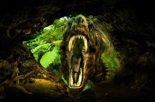 Обои Морда злобного тиранозавра с раскрытой зубастой пастью, пытается пролезть в пещеру с первобытными людьми