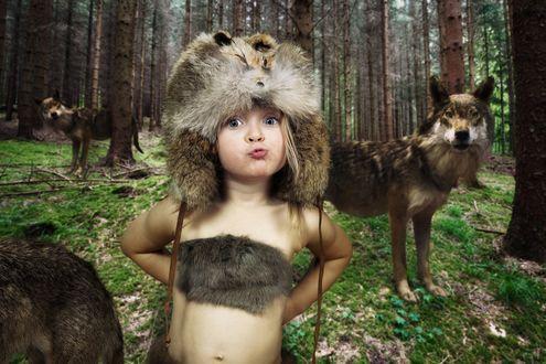Обои Мальчик Маугли в шапке из волчьего меха, стоит среди волчьей стаи, на опушке леса