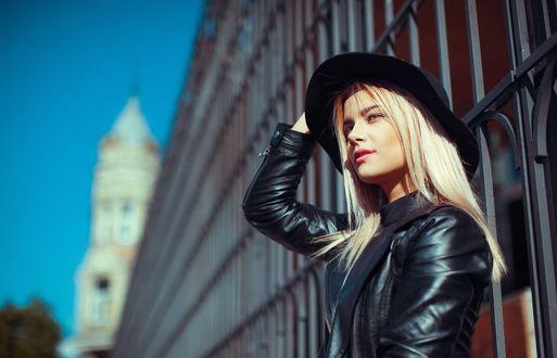 Обои Девушка в шляпе и кожаной курточке стоит на фоне дома, фотограф Imantas Boiko