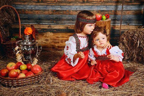 Обои Две маленькие девочки в красивых нарядах сидят на сене на фоне самовара с бубликами и корзины с яблоками, by Oksana Kraft