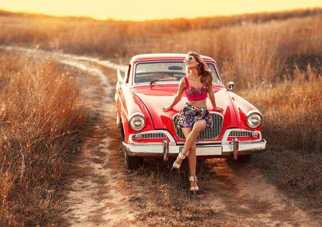 Обои Пинап девушка сидит на копоте красного ретроавтомобиля на степной дороге, фотограф Ирина Джуль