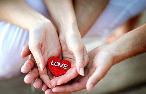 Обои Руки девушки бережно держат сердечко с надписью Love / любовь над руками парня