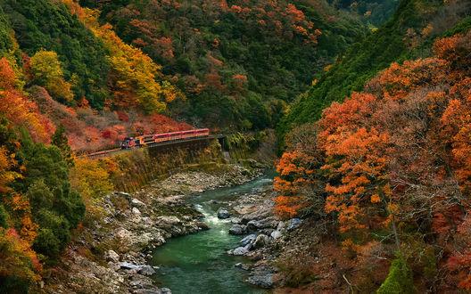 Обои Поезд, идущий по железнодорожной дороге, проложенной через реку, проходящую по горному ущелью