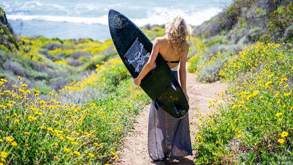 Обои Девушка-серфер идет с доской к морю через заросшую цветами седловину