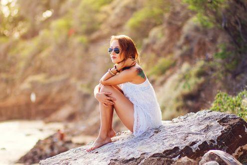 Обои Девушка в очках сидит на камне у моря