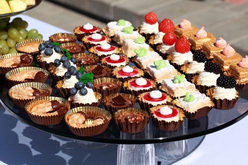 Обои Пирожные с кремом, шоколадом и свежими ягодами разложены рядами на круглом стеклянном столике