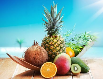 Обои Экзотические фрукты в подставке на столе, на фоне голубого моря: ананас, кокос, манго, авокадо, киви и апельсин