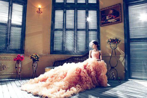Обои Азиатка в розовом бальном платье с пышной юбкой сидит на диване у окна, закрытого ставнями