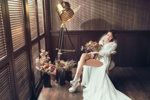 Обои Азиатка в свадебном платье с букетом сидит на стуле рядом цветы в вазах и софит на треноге
