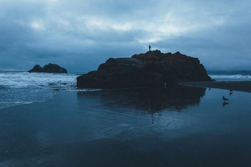 Обои Человек в море стоит на скале