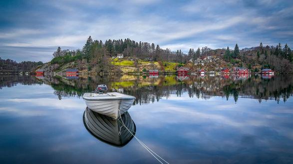 Обои Причаленная моторная лодка на озере, вдалеке виднеются частные дома