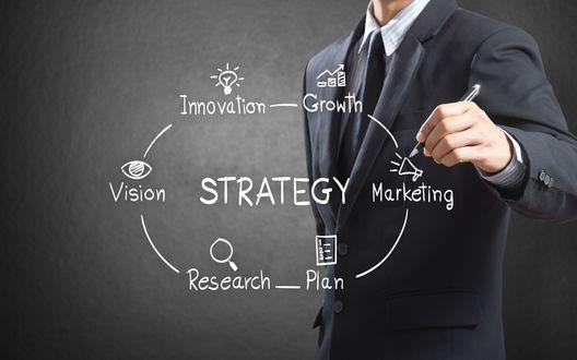 Обои Надпись Strategy / Стратегия и надписи вокруг нее: Research / Исследования, Vision / Видение, Innovation / Инновации, Growth / Рост, Marketing / Маркетинг, Plan / План, мужчина в костюме на заднем плане