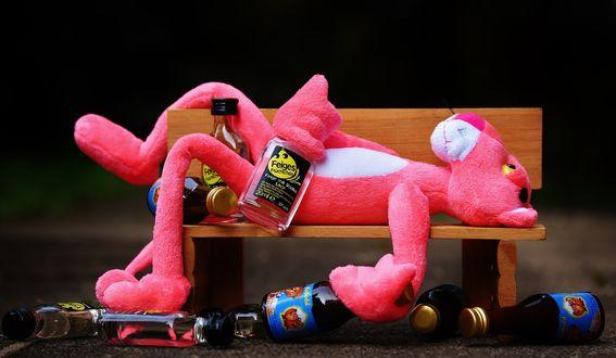 Обои Игрушка пьяной розовой пантеры лежит на скамейке в окружении бутылок