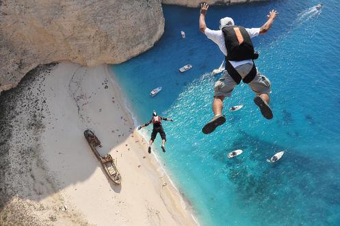 Обои Бухта Навайо / Navagio Beach / Навагио (Закинф), парень прыгает со скалы с парашютом