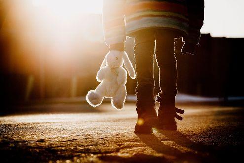Обои Девочка с игрушечным зайцем в руке идет по дороге