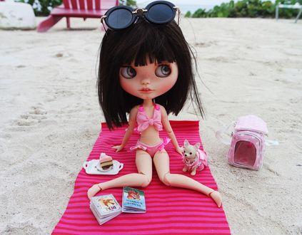 Обои Девушка кукла с солнцезащитными очками на голове в купальнике сидит на коврике на пляже
