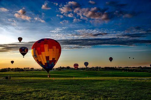 Обои Воздушные шары над лугом на фоне неба с облаками