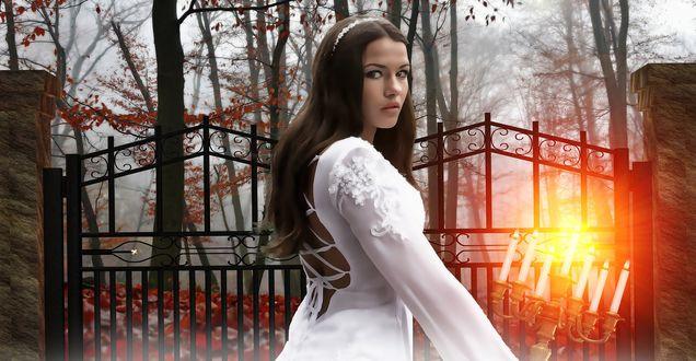 Обои Девушка с темными длинными волосами в белом платье на фоне горящих свечей и железной ограды